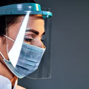 female doctor wearing a face shield to protect herself