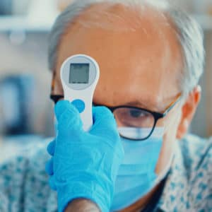 Infrared forehead thermometer taking the temperature of an old man