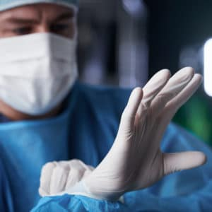 surgeon wearing pair of latex gloves before operation